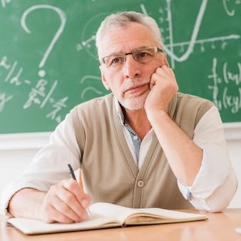 Geconcentreerde oude wiskundeleraar die bij bureau denkt