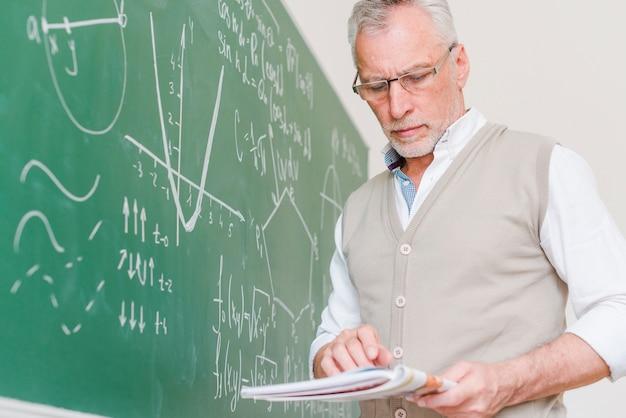 Geconcentreerde oude wiskundeleraar die leerboek bekijkt