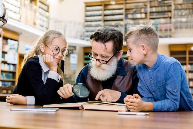 Geconcentreerde oudere man leraar professor en zijn twee kleine slimme schattige studenten lezen boek samen.