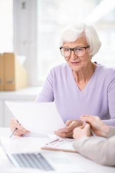 Geconcentreerde oudere vrouw in glazen aan tafel zitten en document lezen alvorens te ondertekenen
