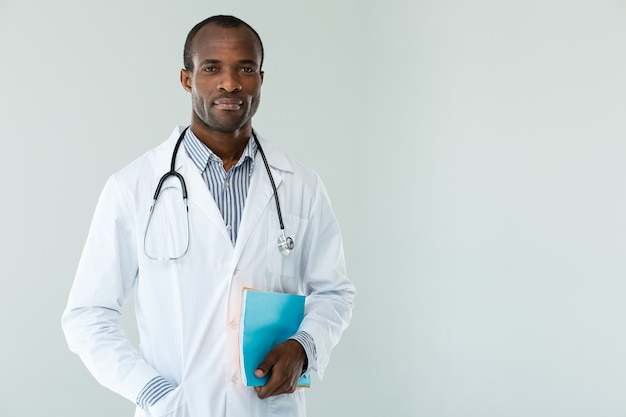 Geconcentreerde professionele arts die patiëntennota's houdt tegen witte muur