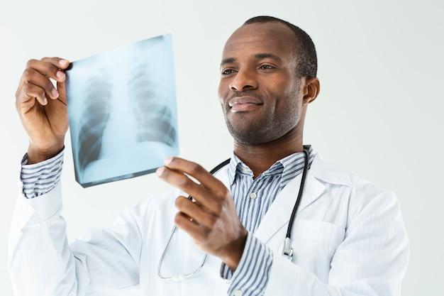 Geconcentreerde professionele arts x-ray scan houden tijdens het werken