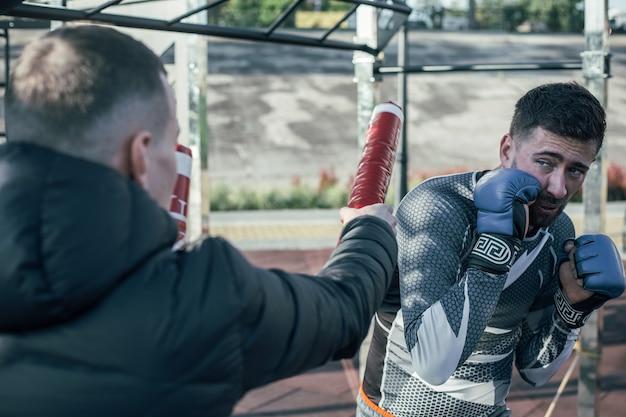 Geconcentreerde professionele mma-bokser die voor zijn trainer staat en de vuisten dicht bij zijn gezicht plaatst terwijl hij naar de boksstokken kijkt