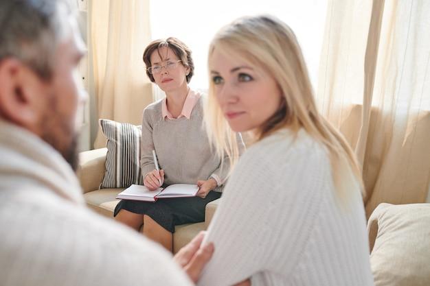 Geconcentreerde psycholoog die de reden van paren probeert te begrijpen