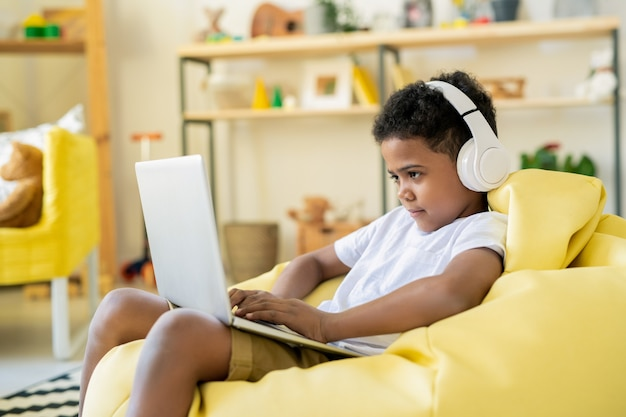 Geconcentreerde schattige schoolkind in koptelefoon kijken naar laptopscherm tijdens het spelen van een game of het volgen van een online educatieve cursus