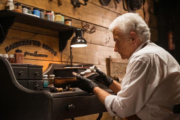Geconcentreerde schoenmaker in werkplaats die schoenen maakt