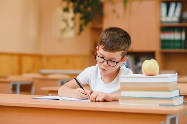 Geconcentreerde schooljongen die aan het bureau zit en in het werkboek schrijft met klasgenoot die erachter zit