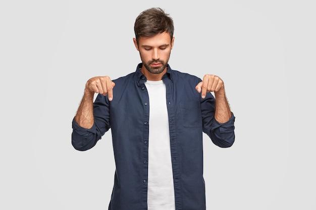 Geconcentreerde serieuze jonge europese man met aantrekkelijk uiterlijk naar beneden gericht, geeft met beide wijsvingers aan, heeft baard en snor, draagt elegant-shirt, geïsoleerd over witte muur