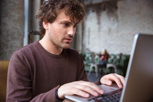 Geconcentreerde serieuze knappe krullende man in bruin sweetshirt met behulp van laptop