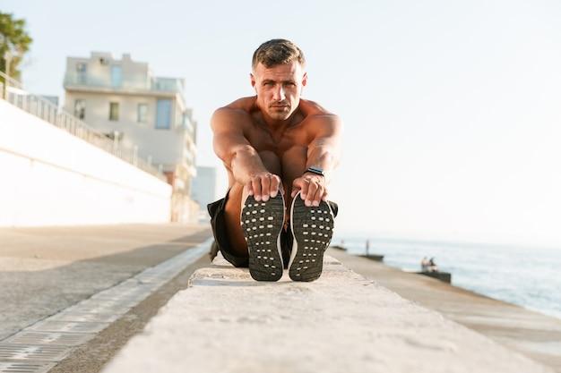 Geconcentreerde shirtless sportman in oortelefoons