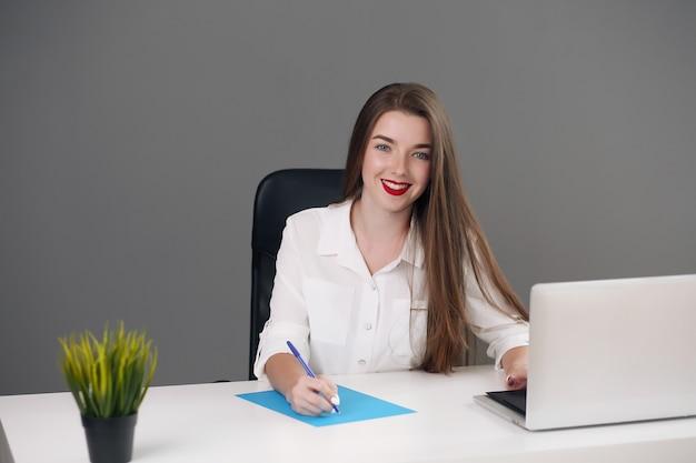Geconcentreerde slimme jonge zakenvrouw met behulp van haar computer op kantoor.