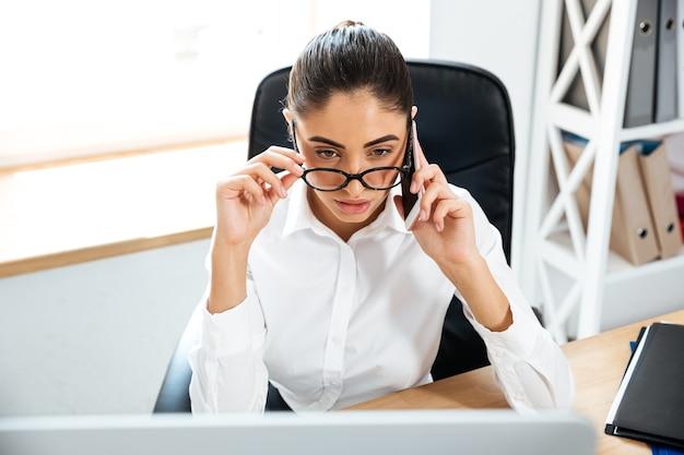 Geconcentreerde slimme zakenvrouw die aan de telefoon praat terwijl ze naar de laptop op kantoor kijkt