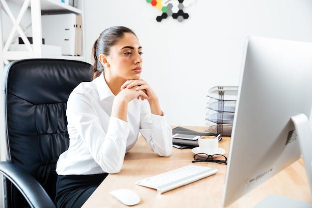 Geconcentreerde slimme zakenvrouw die naar het computerscherm kijkt terwijl ze aan het bureau zit