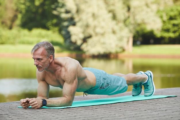 Geconcentreerde spiergebonden volwassen man met shirt doet plank op oefeningsmat in de buurt van rivier