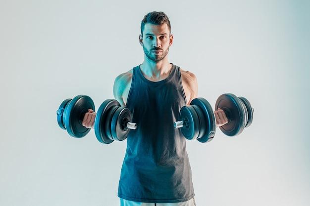 Geconcentreerde sportman die biceps-spieren opleidt met halters. jonge, bebaarde europese man draagt sportuniform en kijkt naar de camera. geïsoleerd op turkooizen achtergrond. studio opname. ruimte kopiëren