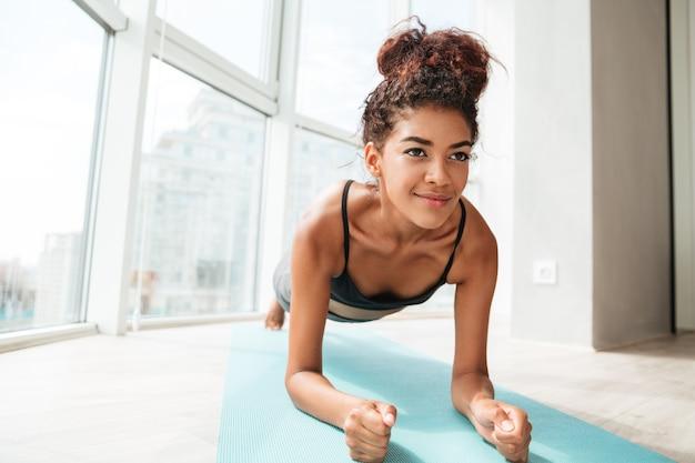Geconcentreerde sportvrouw die zich in plankpositie bevindt