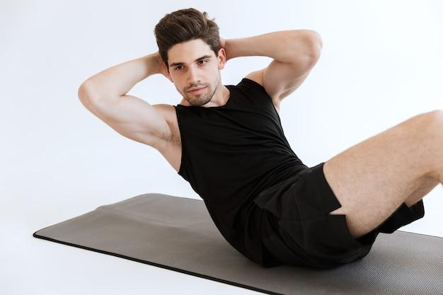 Geconcentreerde sterke jonge sportman maakt abs-oefening geïsoleerd.