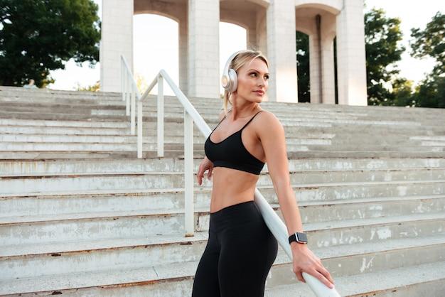 Geconcentreerde sterke jonge sportvrouw luisteren muziek