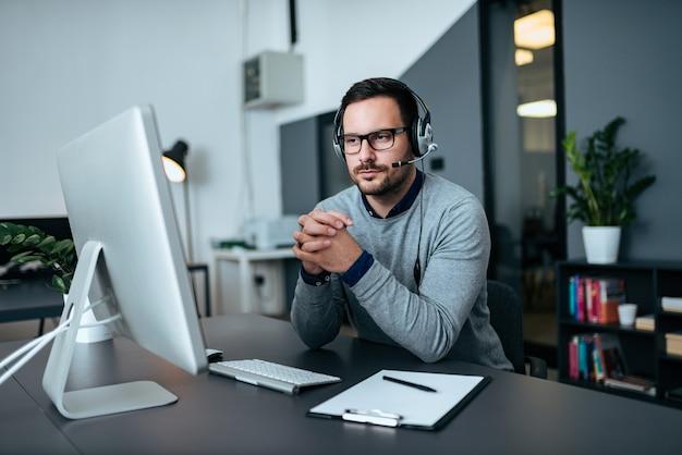 Geconcentreerde steuncentrumarbeider die de computer bekijkt.