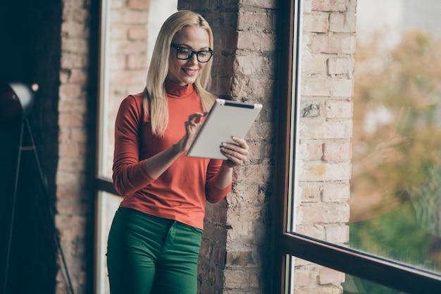 Geconcentreerde succesvolle bedrijfseigenaar charmante vrouw staan in de buurt van venster gebruik haar tablet communiceren met partners dragen rode coltrui in kantoor loft