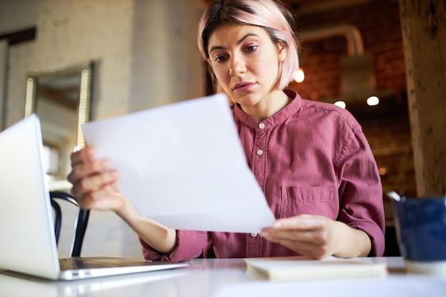 Geconcentreerde succesvolle jonge vrouwelijke econoom die belangrijke gegevens analyseert, open laptop zit, boekhouddocument bestudeert.