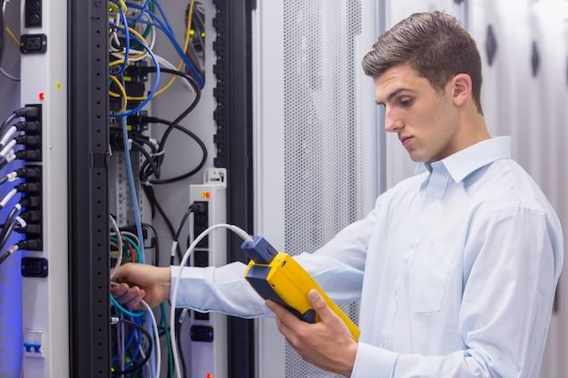 Geconcentreerde technicus die digitale kabelanalysator op servers gebruikt