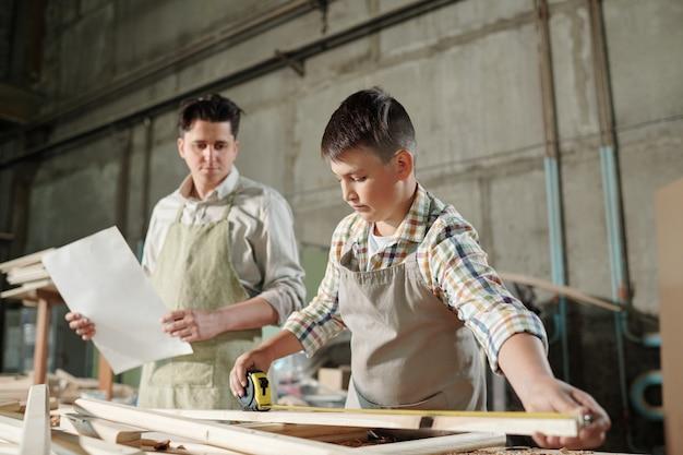 Geconcentreerde tienerzoon in schort met behulp van meetlint tijdens het controleren van de grootte van de houten plank, werkt hij met vader in timmerwerkwinkel