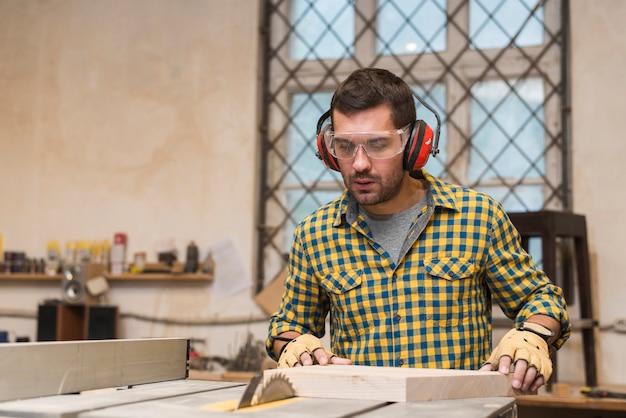 Geconcentreerde timmerman aan het werk met houten plank