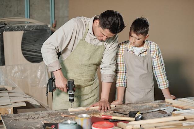 Geconcentreerde timmerman in schort houten plank boren aan balie terwijl tienerzoon zijn proces in werkplaats kijken