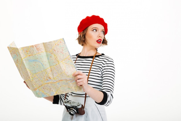 Geconcentreerde toeristenvrouw met de kaart van de cameraholding.