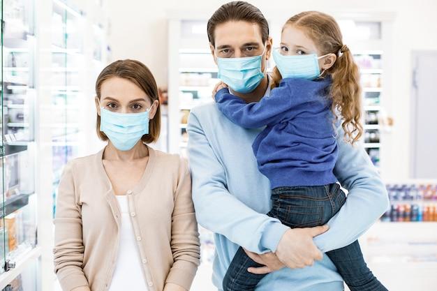 Geconcentreerde trieste familie masker dragen en camera kijken