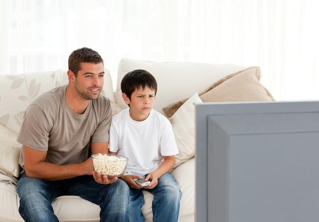Geconcentreerde vader en zoon televisie kijken tijdens het eten van popcorn