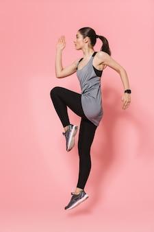 Geconcentreerde verbazingwekkende mooie jonge mooie fitness vrouw die loopt, maakt sportoefeningen geïsoleerd over roze muur