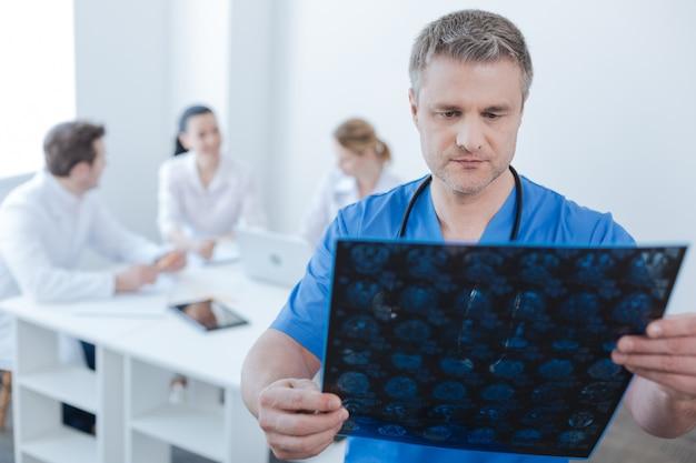 Geconcentreerde volwassen ervaren neuroloog die in het laboratorium werkt en mrt-scanresultaten onderzoekt terwijl collega's genieten van een gesprek