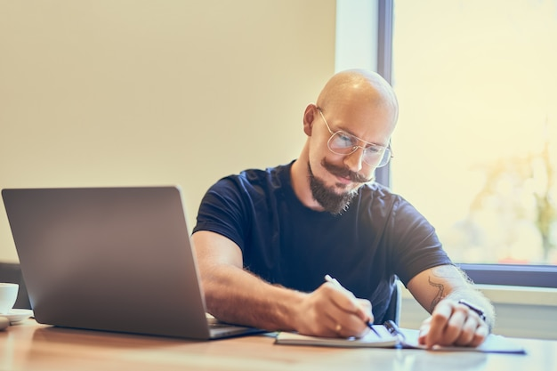 Geconcentreerde volwassen kale man-manager die laptop gebruikt tijdens het schrijven van notities in notitieblok op de werkplek