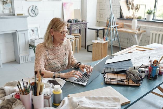 Geconcentreerde volwassen kunstenaar in brillen aan tafel zitten en typen op laptop tijdens het kopen van verbruiksartikelen om te schilderen