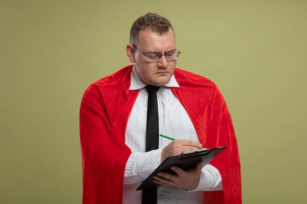 Geconcentreerde volwassen superheld man in rode cape bril schrijven op klembord met pen geïsoleerd op olijfgroene muur
