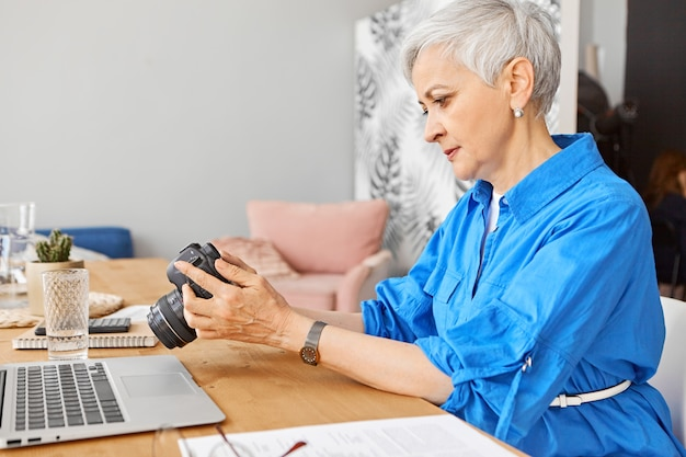 Geconcentreerde volwassen vrouw professionele fotograaf previews op camera controleren. ernstige vrouw op pensioen kijken tutorial over fotografie online met behulp van laptop. hobby, extern werk en leeftijdsconcept