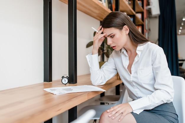 Geconcentreerde vrouw die aan documenten in het kantoor werkt