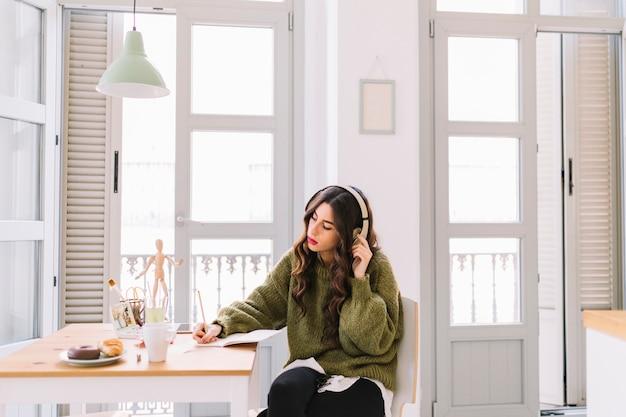 Geconcentreerde vrouw die en aan muziek trekt luistert