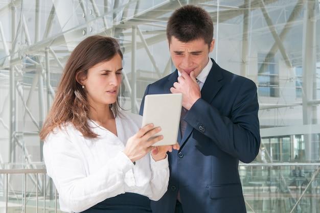 Geconcentreerde vrouw die man gegevens over tablet toont, die hard denkt