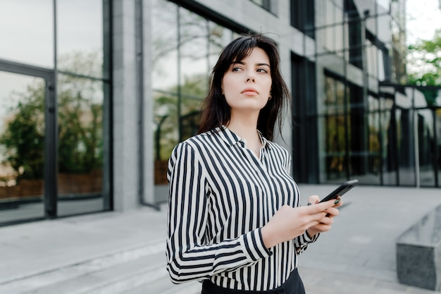 Geconcentreerde vrouw die met telefoon in handen denkt