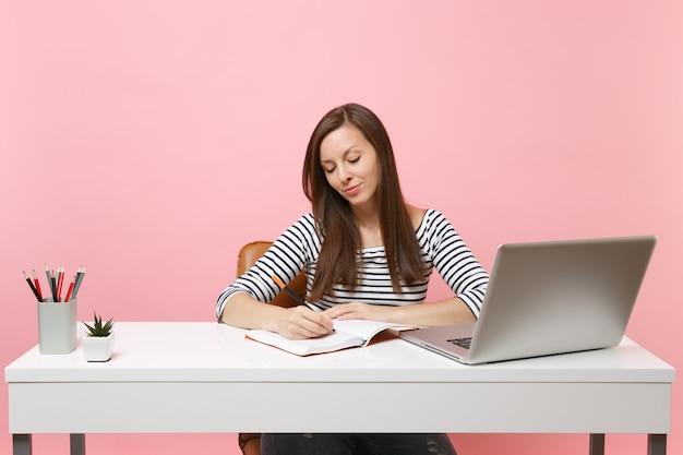 Geconcentreerde vrouw die notities schrijft op notebook zit, werkt aan een wit bureau met een moderne pc-laptop