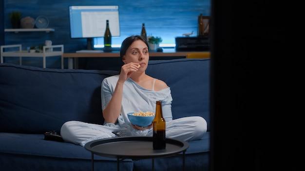Geconcentreerde vrouw die popcorn eet en een interessante film op tv kijkt, alleen thuis...
