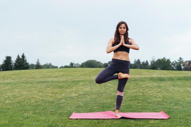 Geconcentreerde vrouw die yoga in openlucht doet