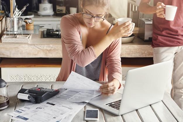Geconcentreerde vrouw gekleed terloops berekenende rekeningen, zittend aan de keukentafel met laptop, rekenmachine, papieren en mobiel, met witte beker en het doorgeven aan haar man