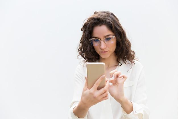 Geconcentreerde vrouw in glazen die bericht texting, internet raadplegen