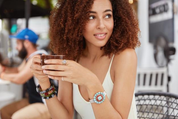 Geconcentreerde vrouw met afro-kapsel, geniet van koffiepauze in cafetaria, merkt iemand achter, kijkt bedachtzaam weg.