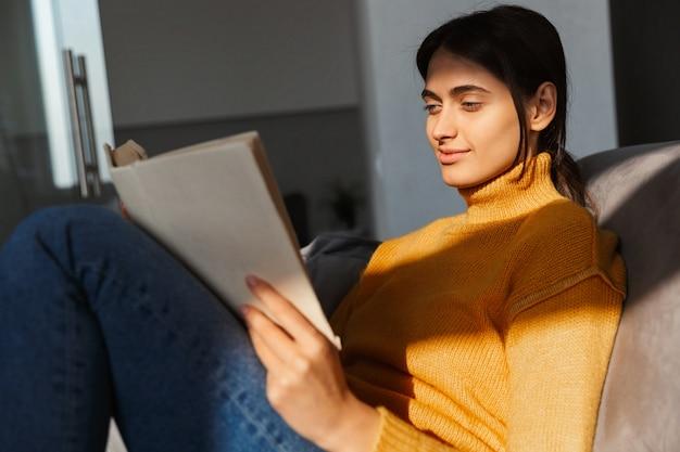 Geconcentreerde vrouw op bank in het boek van de huislezing.