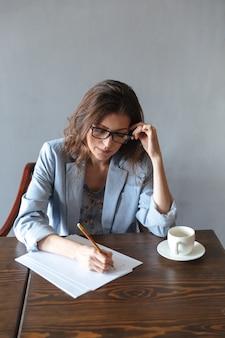 Geconcentreerde vrouw schrijven van aantekeningen binnenshuis in de buurt van kopje koffie